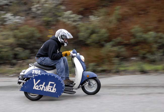 A scooter with a sidecar dodging the raindrops