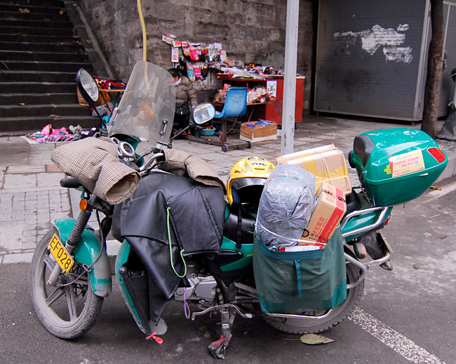 A postal service motorcycle in downtown Chongqing...check out the handwarmers, and the parcels